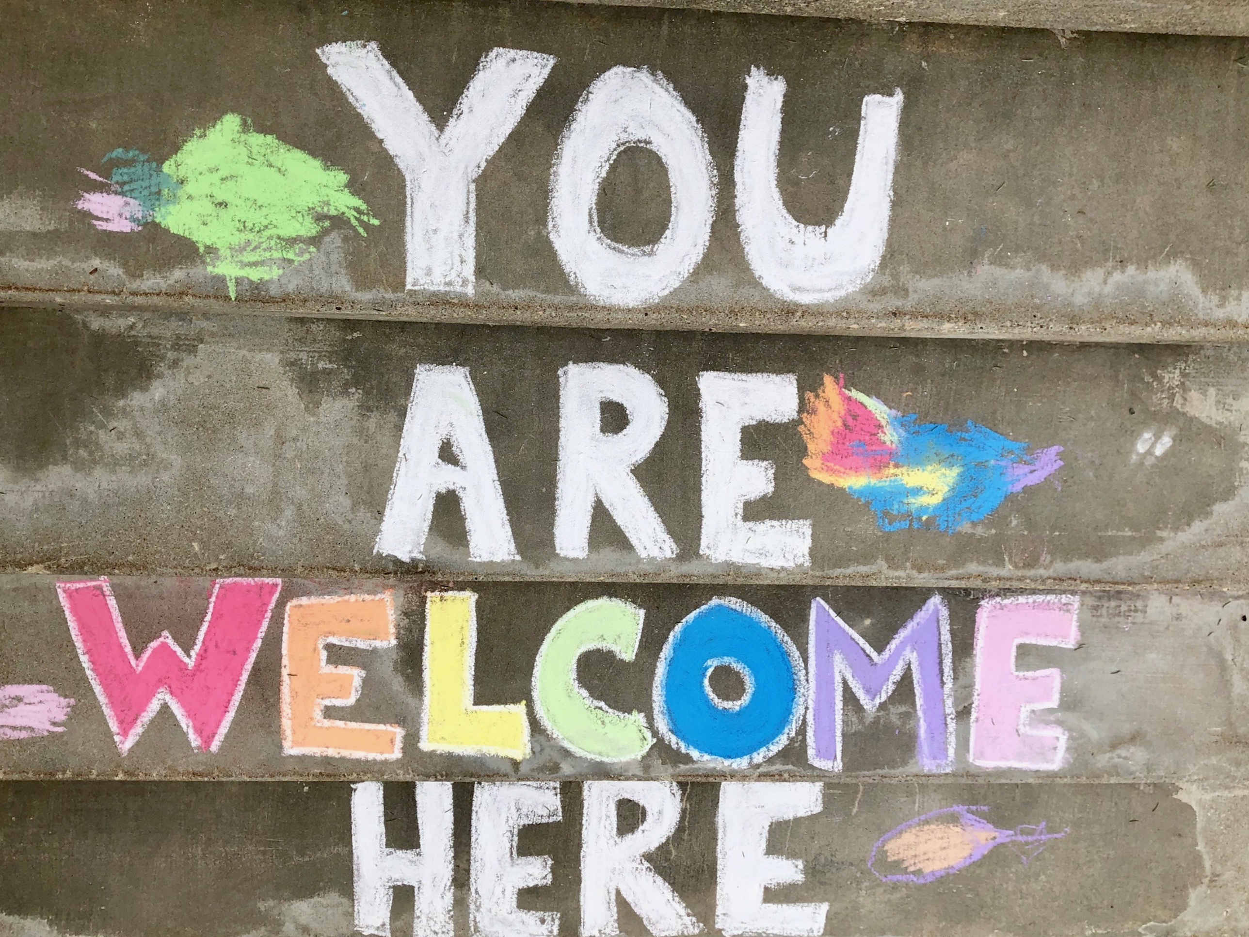 "sidewalk chalk on the steps of the Decorah UCC reading ""You are welcome here"""